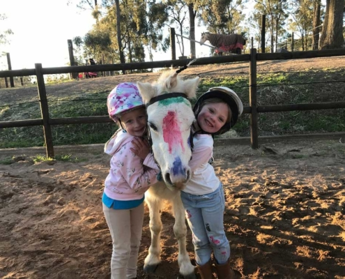 Children enjoying birthday cuddles with a pony